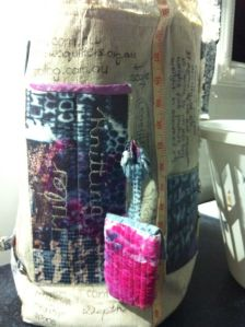 Side showing long vertical pockets for knitting needles and a ruler plus a small bag for thimbles and seam ripper.