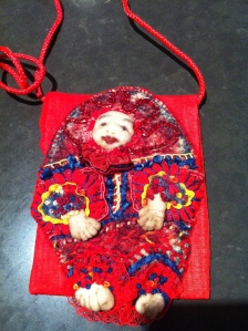 """An embroidered """"person"""" fronting a bag"""