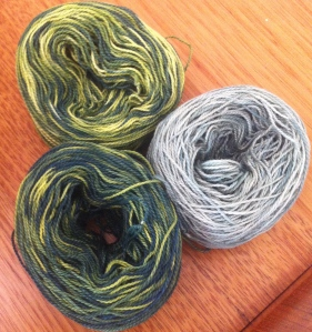 Perle 8 balls of white cotton painted with mixtures of navy and yellow.  The one on the right is  a heavy dilution of the dye in the bath