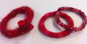 Three red bangles. Two crocheted with variegated cotton embroidery thread and a) bead mix; and b) red beads. The one on the left is crocheted with mohair yarn and cotton yarn. the beads were threaded onto the cotton yarn. Wire strengthens the structure and buttons finish it.