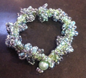A small bracelet in which a mixture of pale green and clear silver-lined beads is crocheted into blue-green embroidery cotton. Finished with a beaded loop and a large green bead closure.