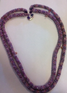 A long double-stranded necklace of two crocheted beaded tubes using variegated purple embroidery cotton and a mixture of mauve and purple beads.. closure is magnetic.