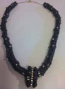 Grey tape/ribbon crocheted with a spiral pattern of dark grey and clear beads. Loop pendant.