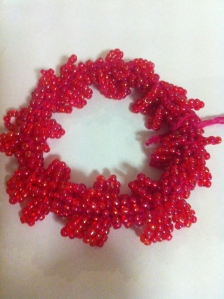 Crochet beaded bracelet using hand dyed cotton and iridescent size 8 beads. Extra bead loops worked in .